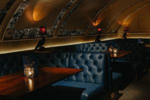 THE VAULT – PRIVATE HIRE AREA AVAILABLE Follow the steps down to the lavish Vault, complete with wood cladded walls and golden arches. The perfect place to impress your fellow comrades with your very own fridge and leather padded booth seating.  Great for parties with up to 70 guests.